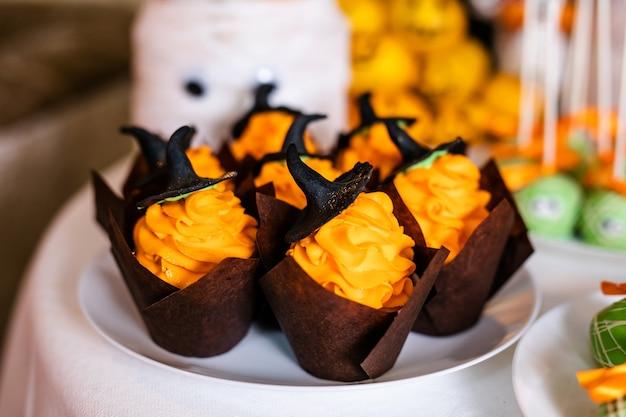 Cupcakes com creme laranja e doces chapéus pretos na barra de chocolate para a celebração do halloween Foto Premium