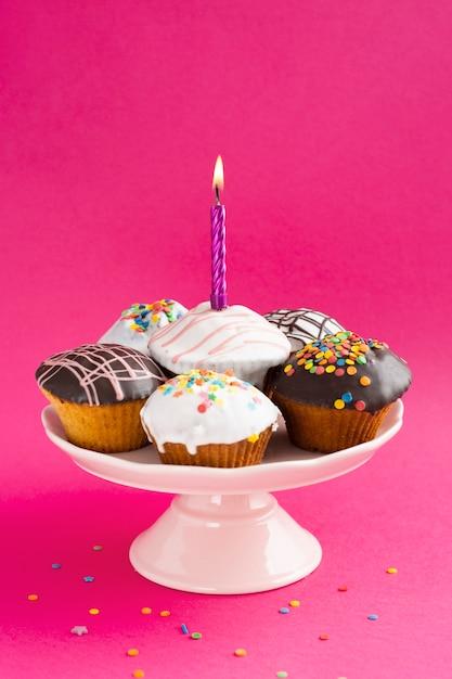 Cupcakes com esmalte em fundo colorido Foto gratuita