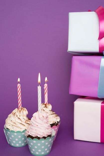 Cupcakes com vela acesa ao lado de presentes Foto gratuita