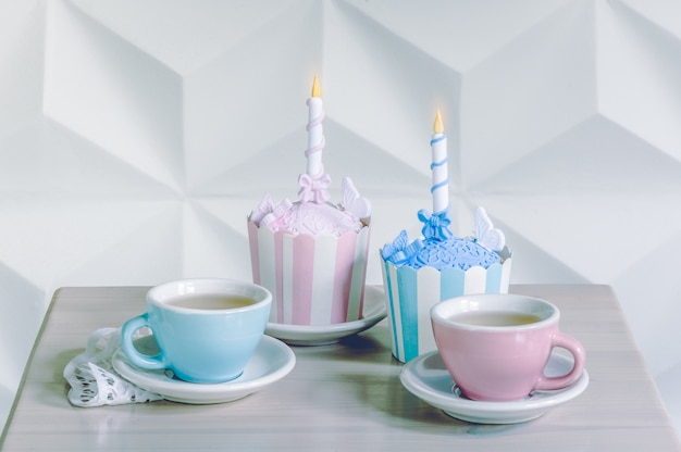 Cupcakes de aniversário com vela de aniversário e xícaras de chá Foto Premium