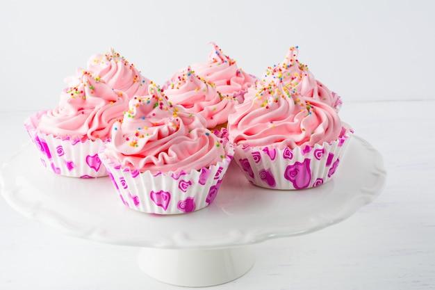 Cupcakes de aniversário rosa decorados no suporte do bolo Foto Premium