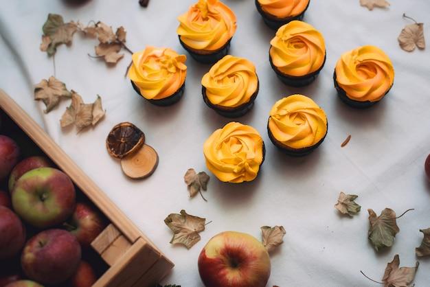 Cupcakes de laranja com folhas secas de outono e maçãs Foto Premium