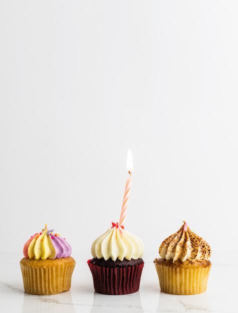 Cupcakes de variedade com vela festa de aniversário no fundo branco, conceito de aniversário Foto Premium