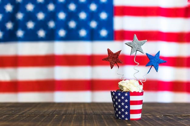 Cupcakes decorativos com vermelho; estrelas de prata e azuis na mesa de madeira contra bandeiras americanas para o 4 de julho Foto gratuita