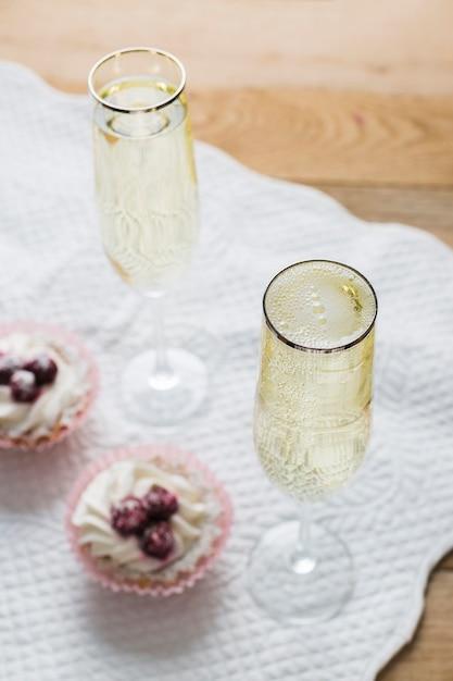 Cupcakes e copos de vinho branco de alta vista Foto gratuita