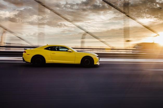 Cupê amarelo do esporte na estrada no por do sol. Foto gratuita