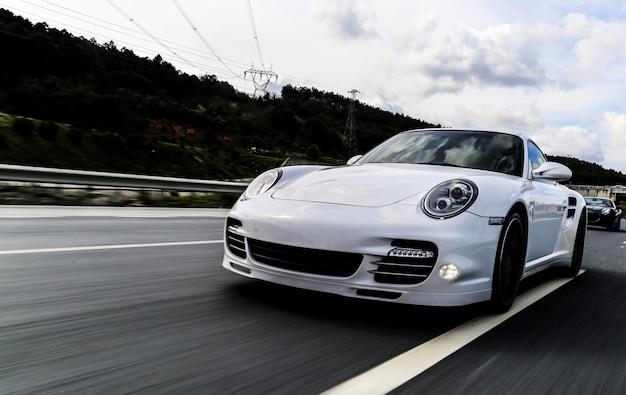 Cupê branco dirigindo na estrada. Foto gratuita