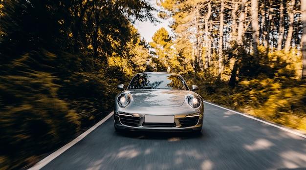Cupê de cor prata com luzes dianteiras na estrada sob a luz do sol. Foto gratuita