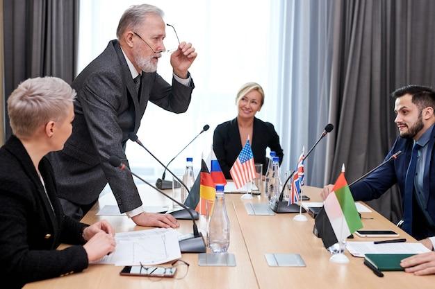 Cúpula política de representantes de diferentes países e discussão de questões internacionais, reunidos sem vínculos. em uma sala de reuniões moderna e iluminada Foto Premium