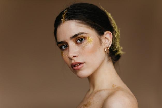 Curiosa e linda senhora usa joias. mulher romântica positiva posando na parede marrom. Foto gratuita