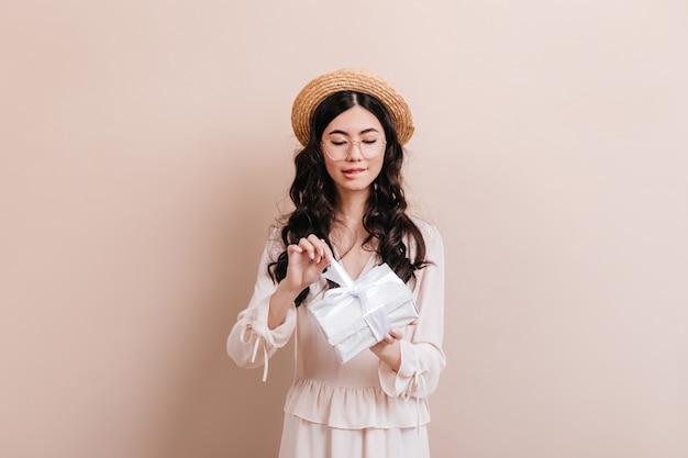 Curiosa mulher asiática abrindo o presente de aniversário. modelo feminino chinês bonito segurando o presente sobre fundo bege. Foto gratuita