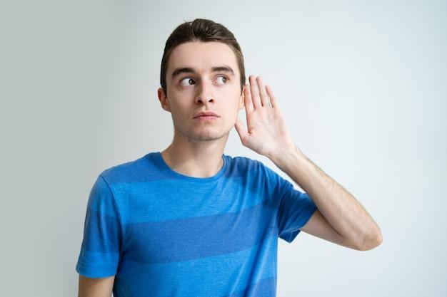 Curioso jovem segurando a mão perto da orelha Foto gratuita