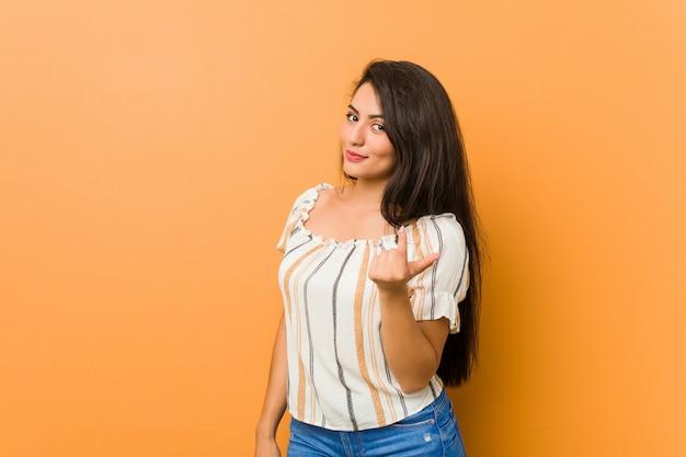 Curvilínea jovem apontando com o dedo para você, como se convidando se aproximar. Foto Premium