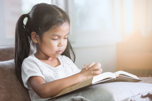 Cute, asian menina criança, fechou, olhos, e, dela, dobrado, dela, mão, em, oração, ligado, um, santissimo, bíblia Foto Premium