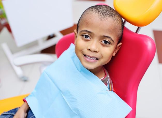 Cute, bebê preto, menino, americano africano, sorrindo, sentando, em, a, cadeira dental Foto Premium
