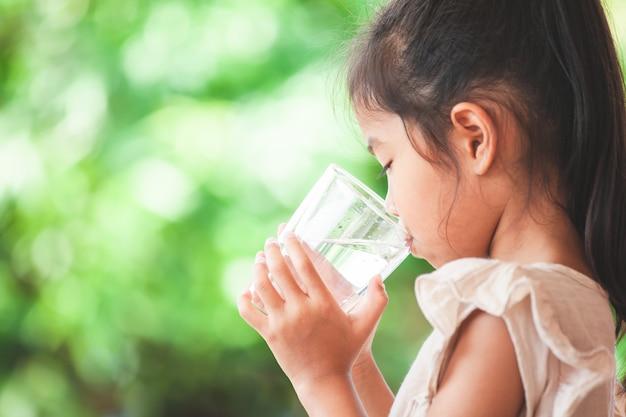 Cute, criança asiática, menina, bebendo, água fresca, de, vidro Foto Premium