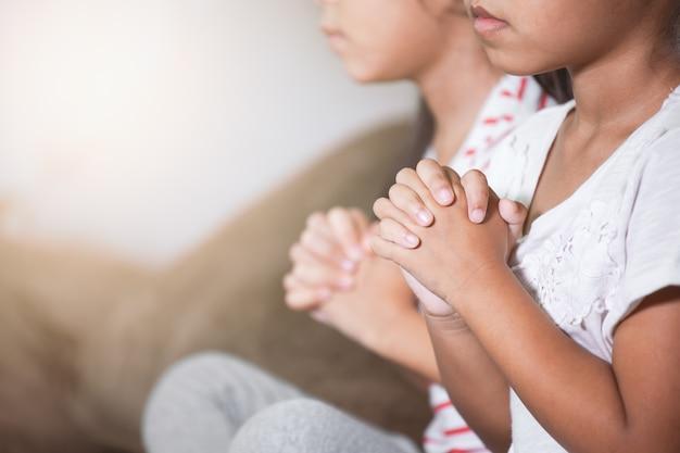 Cute, criança asiática, menina, e, dela, irmã, orando, com, dobrado, dela, mão, em, a, sala, junto Foto Premium