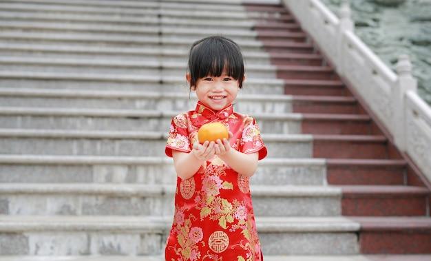 Cute, criança asiática, menina, em, chinês tradicional, vestido, com, segurando, sagrado, laranja, em, chinês, templo Foto Premium