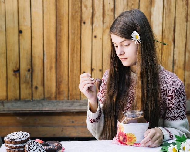 Cute, menina, comer, chocolate, espalhar, com, colher, ligado, natal Foto gratuita