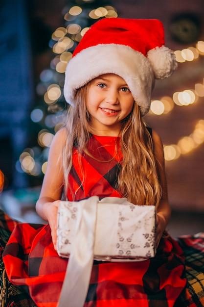 Cute, menininha, em, chapéu santa, desembalando, presente natal Foto gratuita