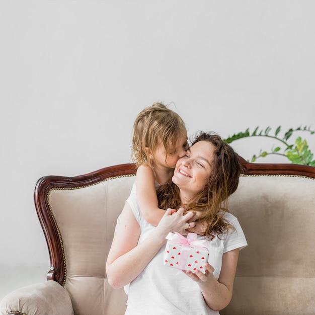 Cute, pequeno, menina, beijando, para, dela, mãe, segurando, caixa presente, sentar sofá Foto gratuita