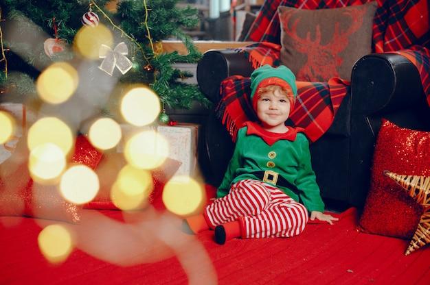 Cutte menino em casa perto de decorações de natal Foto gratuita