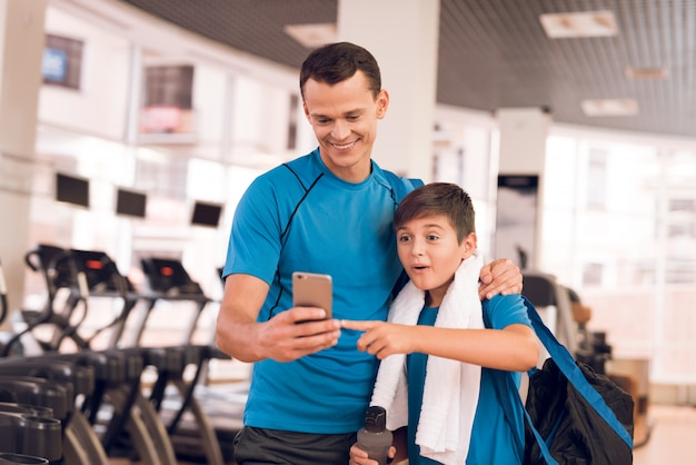 D está de pé com telefone no ginásio e seu filho faz amizade com ele. Foto Premium