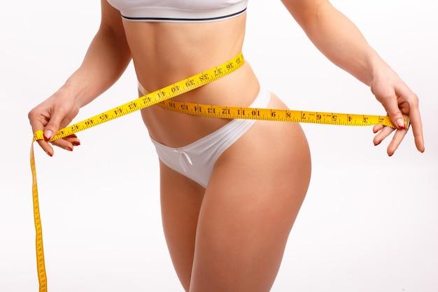 Da cintura das mulheres com uma fita métrica Foto gratuita