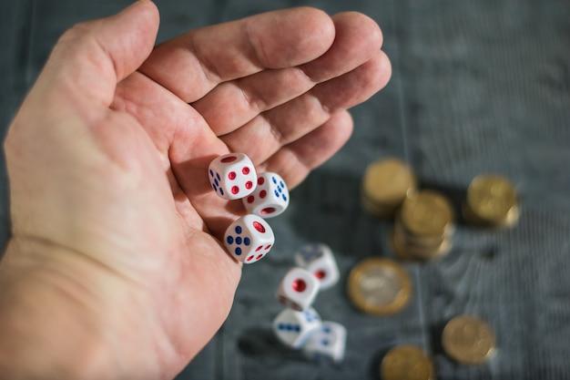 Dados rolam com os homens da mão esquerda na mesa com dinheiro. Foto Premium