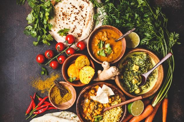 Dal, palak paneer, caril, arroz, chapati, chutney em bacias de madeira na mesa escura. Foto Premium