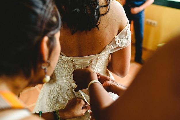 Dama de honra ajuda a noiva a se vestir no dia do casamento Foto Premium