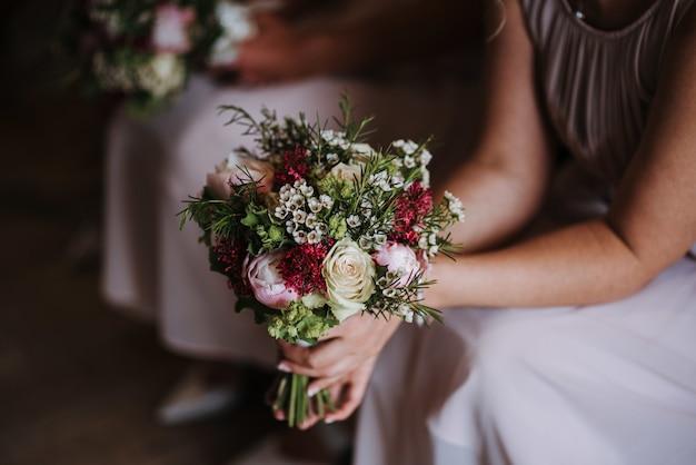 Dama de honra segurando o lindo buquê de rosas do dia do casamento Foto gratuita
