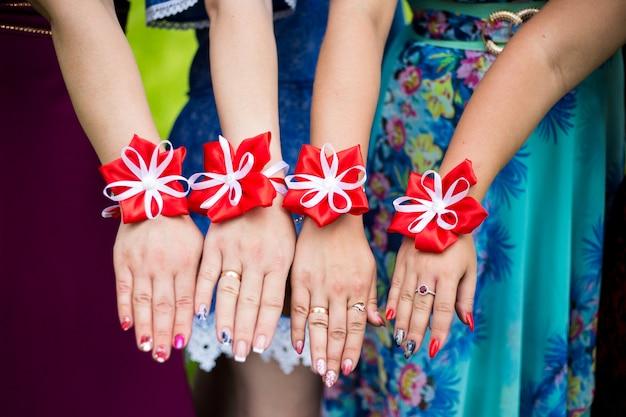 Damas de honra mostram pulseiras de flores nas mãos Foto Premium