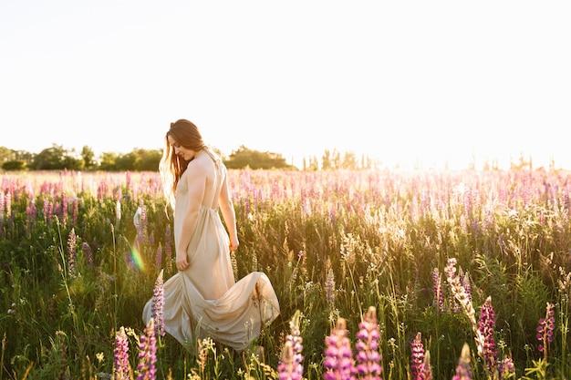Dança da jovem mulher em um campo do wildflower com nascer do sol no fundo. Foto gratuita