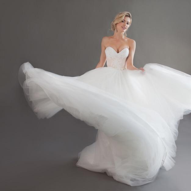 Dança jovem noiva vestido de noiva luxuoso. menina bonita de branco. emoções de felicidade, riso e sorriso, fundo cinza Foto Premium