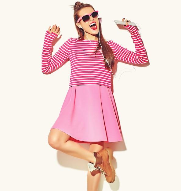 Dança linda feliz sorridente mulher morena sexy menina bonita em roupas de verão rosa colorido casual com lábios vermelhos Foto gratuita