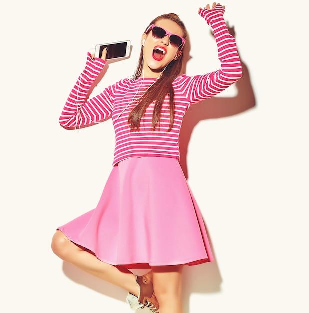 Dançando linda feliz sorridente mulher morena sexy menina bonita em roupas de verão rosa colorido casual com lábios vermelhos isolados no branco ouvindo música Foto gratuita