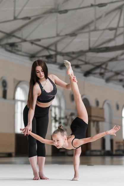 Dançarina de balé atraente, auxiliando seu aluno na pista de dança Foto gratuita