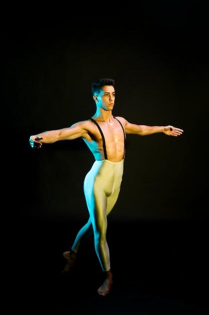 Dançarina de balé masculino clássico, realizando em holofotes Foto gratuita