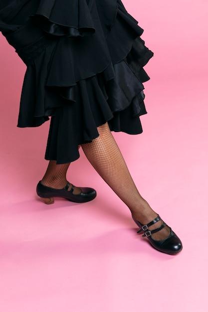 Dançarina de flamenco posando de pernas em fundo rosa Foto gratuita