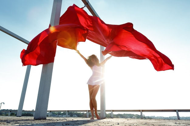 Dançarino de seda morena bonita com cortinas vermelhas posando no telhado Foto gratuita