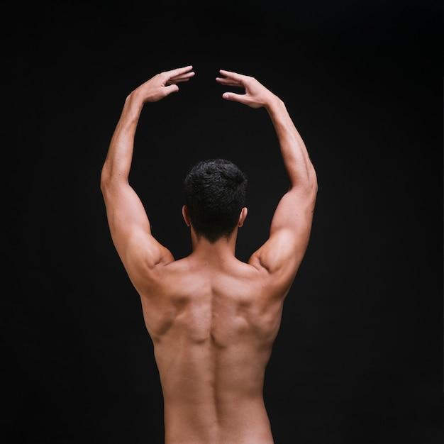 Dançarino sem camisa, levantando os braços durante o desempenho Foto gratuita