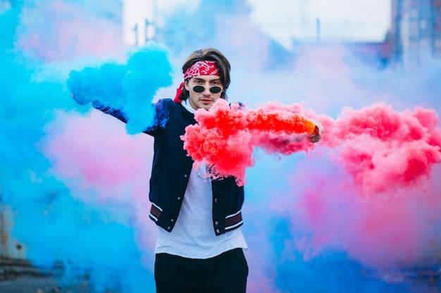 Dançarino urbano masculino com fumaça colorida Foto gratuita