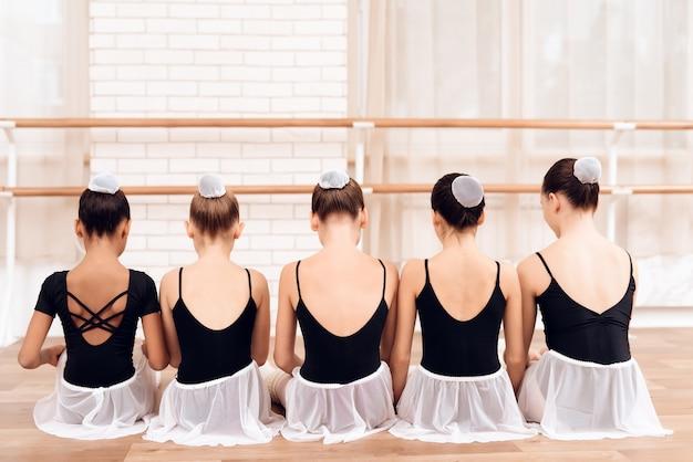 Dançarinos de crianças sentado em fila com as costas para a câmera. Foto Premium