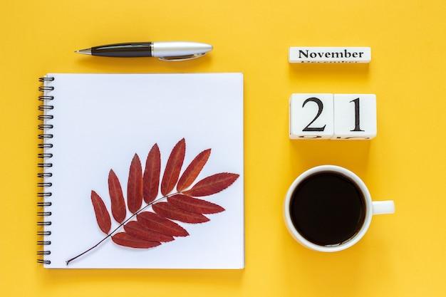 Data do calendário, xícara de café, bloco de notas com caneta e folhas de outono Foto Premium