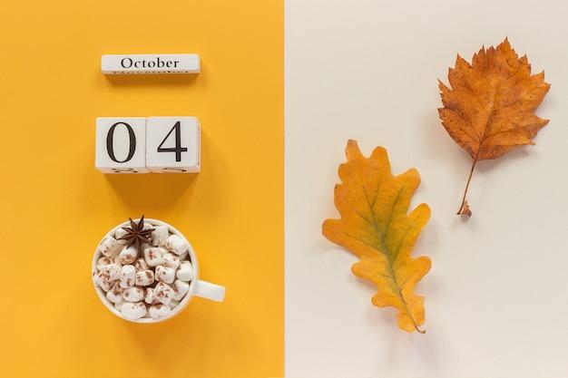 Data do calendário, xícara de chocolate com marshmallows e folhas de outono amarelas Foto Premium