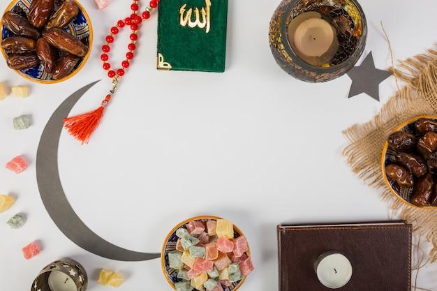 Datas frescas de palmeira suculenta; contas de oração; vela; lua crescente; kuran sagrado com espaço no fundo branco Foto gratuita