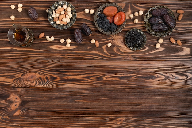 Datas frescas do ramadã; frutas secas; nozes e chá de ervas de vidro na mesa de madeira Foto gratuita