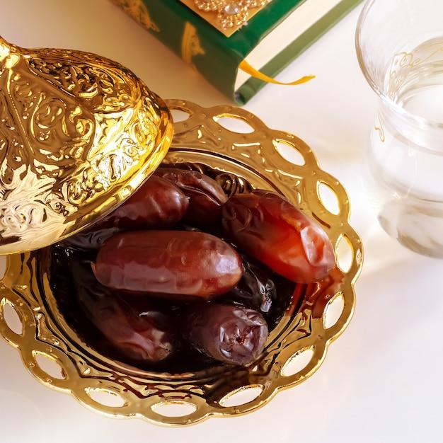 Datas orgânicas placa dourada árabe, copo de água potável pura e livro de alcorão. Foto Premium