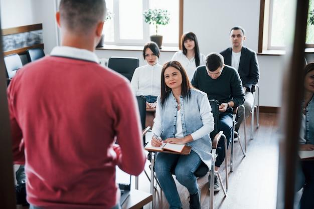 De camisa vermelha. grupo de pessoas em conferência de negócios em sala de aula moderna durante o dia Foto gratuita
